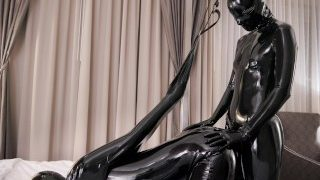 Sexdoll in shiny latex catsuit and strapon